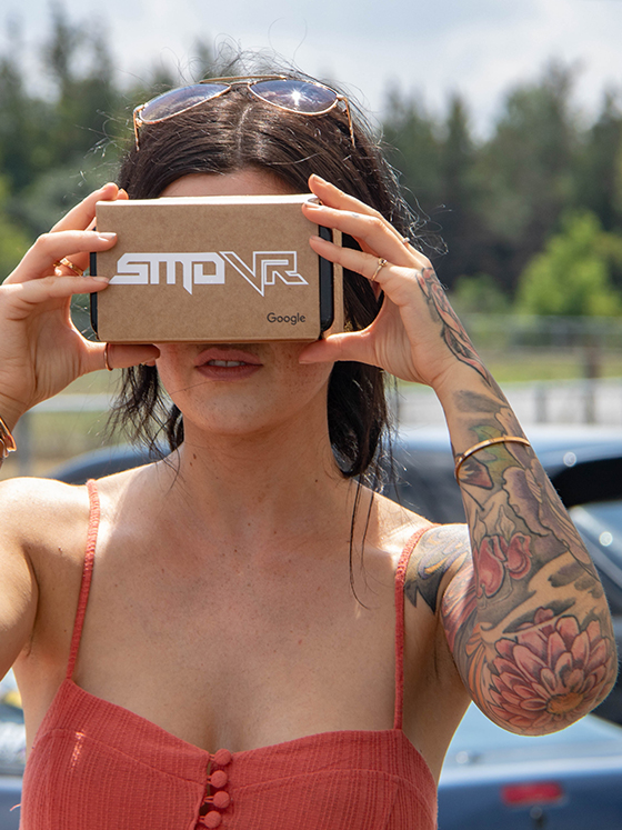A woman with tattoos holding up a google cardboard vr viewer watching a custom VR experience created by SMDVR