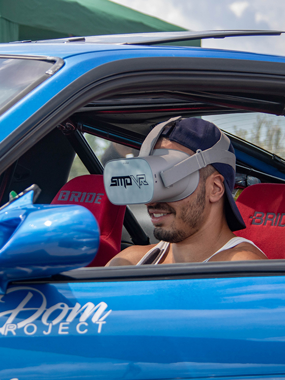 A man sitting in a drift car wearing an Oculus GO headset viewing a custom virtual reality experience created by SMDVR