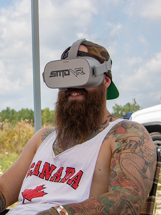 A man with a beard and tattoos sitting with an Oculus GO headset viewing a custom virtual reality experience by SMDVR