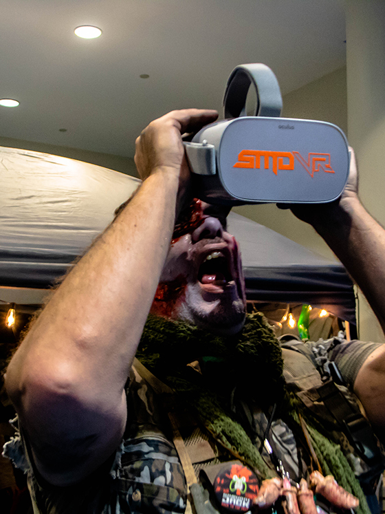 A zombie holding an Oculus Go virtual reality headset and looking like it's going to eat it