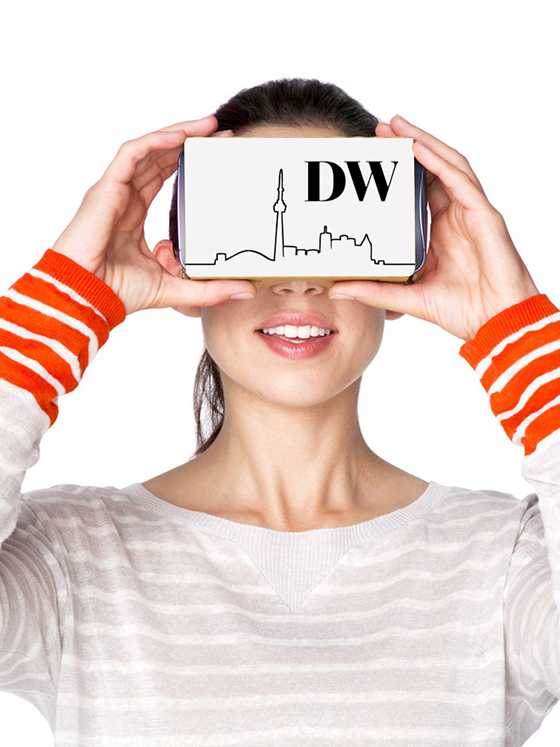A woman holding up a cardboard virtual reality headset with the DW logo
