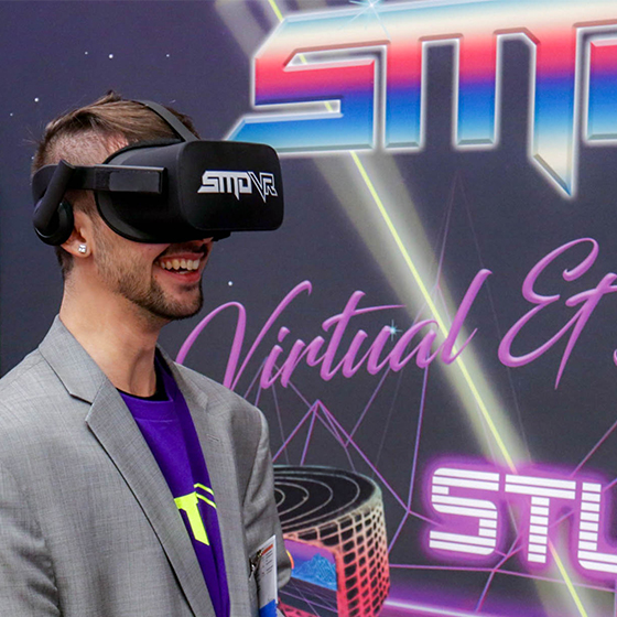 A man smiling while wearing an oculus rift virtual reality headset with an SMDVR logo