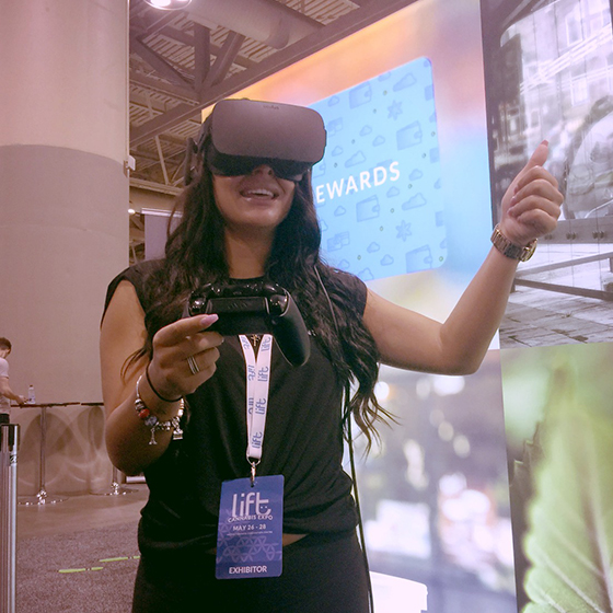 a woman wearing a virtual reality headset enjoying the Lift & Co. Virtual Reality experience powered by SMDVR