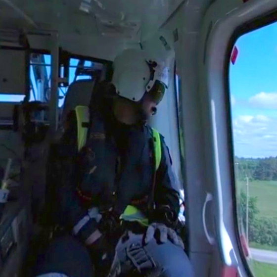 an Ornge helicopter crewman looking out the window of a helicopter